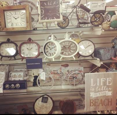 "Clocks and a sign that says ""Life is better at the beach"""